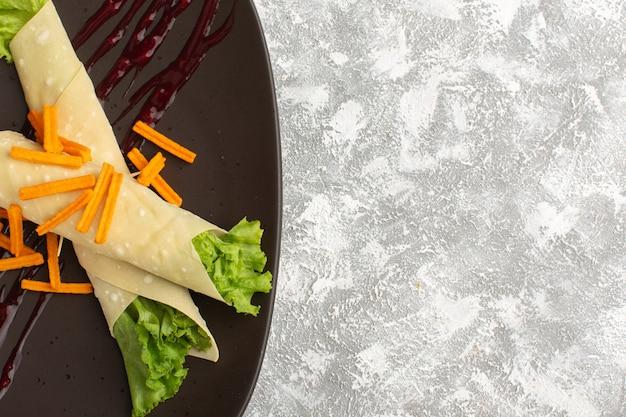 Bovenaanzicht van sandwichbroodjes met groenten en groene salade, samen met beschuit in donkere plaat