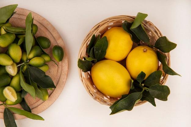 Bovenaanzicht van sappige citroenen op een emmer met kinkans geïsoleerd op een houten keukenbord op een witte muur