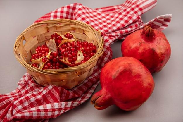 Bovenaanzicht van sappige en gezonde granaatappels op een emmer op een gecontroleerde doek