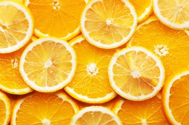 Bovenaanzicht van sappige en lekkere plakjes sinaasappel en citroen achtergrond. gezond vers voedsel. plaats voor tekst of creatief ontwerp, plat gelegd. bron van vitamine c. het concept van verse citrusproducten.