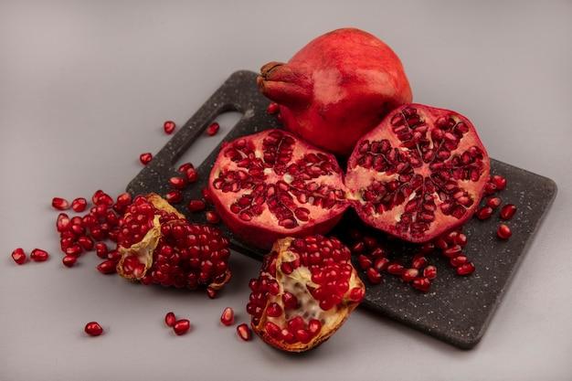 Bovenaanzicht van sappige gehalveerde en hele granaatappels op een bord zwart keuken