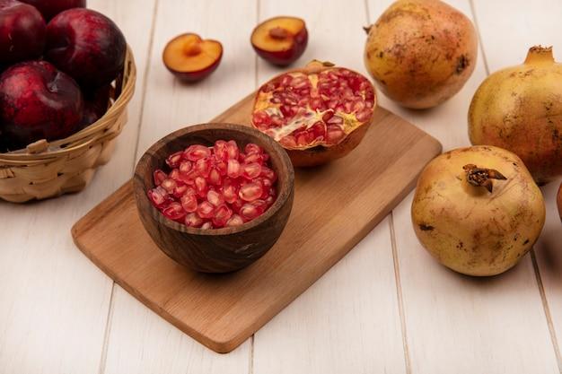Bovenaanzicht van sappige granaatappel zaden op een houten kom op een houten keuken bord met plukken op een emmer met granaatappels geïsoleerd op een witte houten achtergrond