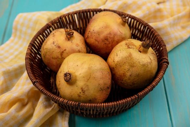 Bovenaanzicht van sappige granaatappels op een emmer op een geel geruit doek op een blauwe houten ondergrond