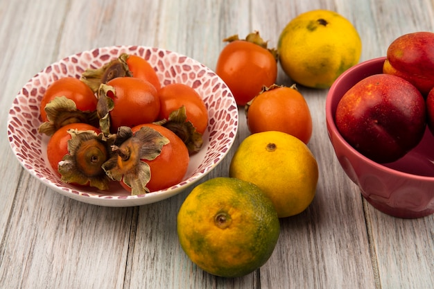 Bovenaanzicht van sappige perziken op een kom met kaki en mandarijnen geïsoleerd op een grijze houten achtergrond