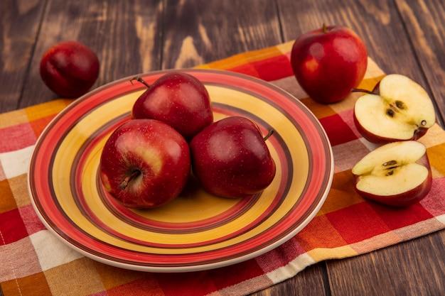 Bovenaanzicht van sappige rode appels op een plaat op een geruite doek met gehalveerde appels geïsoleerd op een houten oppervlak