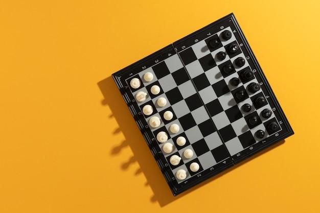 Bovenaanzicht van schaakbord met stukken op gele achtergrond