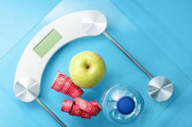 Bovenaanzicht van schaal met een fles water, meetlint en een appel op blauwe achtergrond