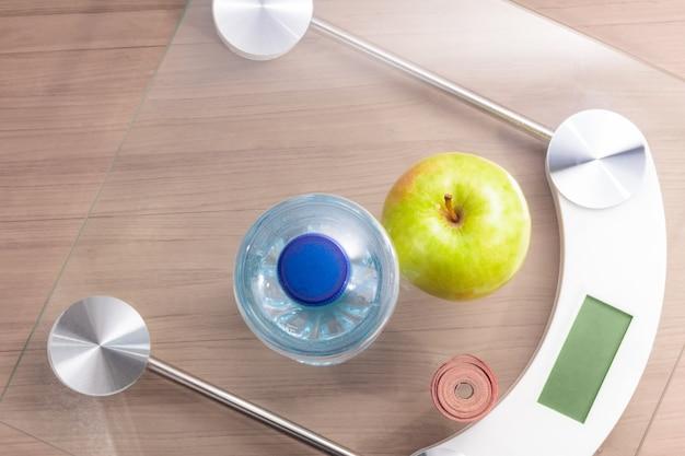 Bovenaanzicht van schaal op houten tafel met fles water, meetlint en een appel
