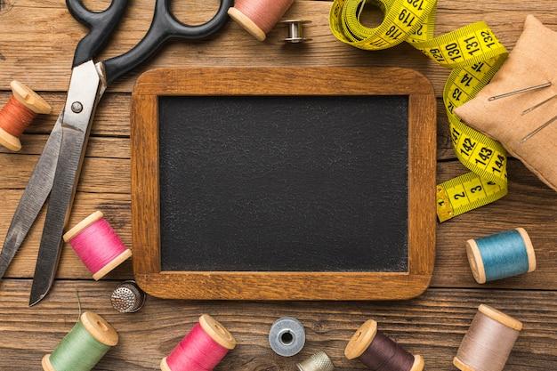 Bovenaanzicht van schaar met meetlint en schoolbord
