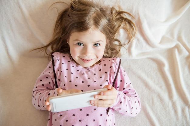 Bovenaanzicht van schattig klein meisje met tablet in de hand