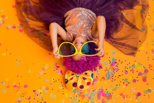 Bovenaanzicht van schattig meisje met clown pruik en grote zonnebril