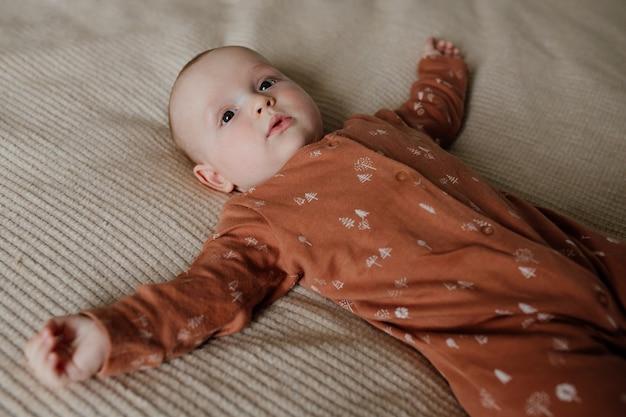 Bovenaanzicht van schattige baby in pyjama liggend op zacht en warm bed in gezellige slaapkamer