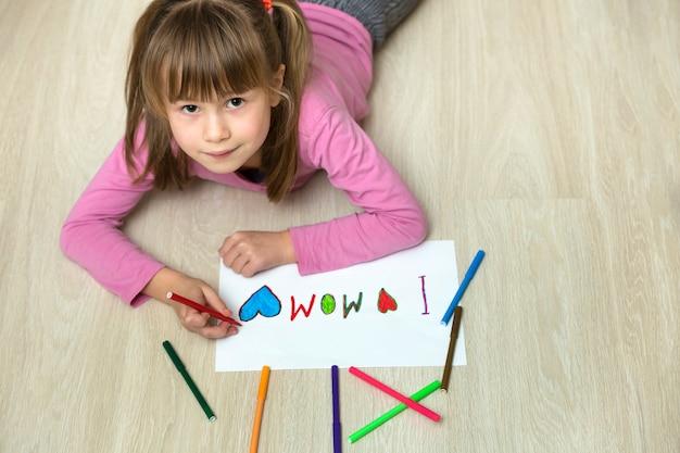 Bovenaanzicht van schattige kind meisje tekenen met kleurrijke kleurpotloden ik hou van mam