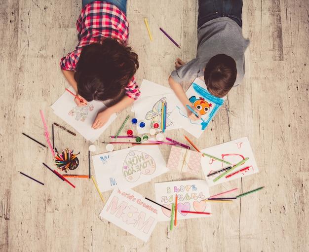 Bovenaanzicht van schattige kinderen tekenen terwijl liggend op de vloer.