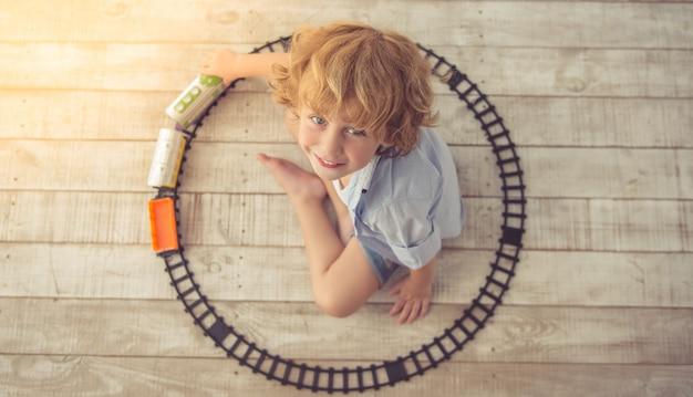Bovenaanzicht van schattige kleine jongen spelen met speelgoed trein