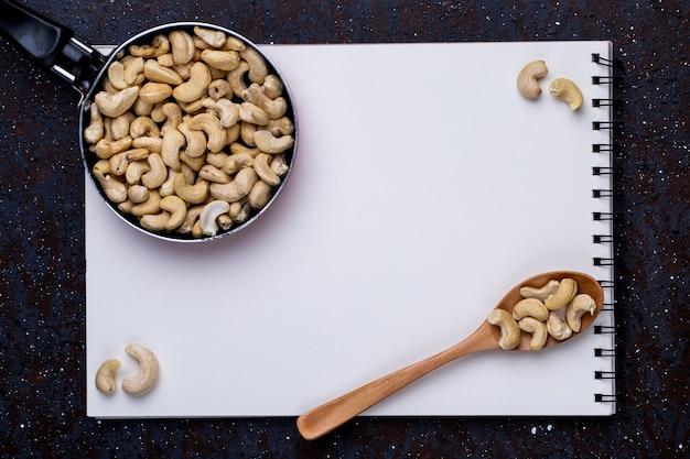 Bovenaanzicht van schetsboek en een pan met cashew en een houten lepel met noten op zwarte achtergrond