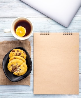 Bovenaanzicht van schetsboek en havermout koekjes met chocoladeschilfers en een kopje thee op rustiek
