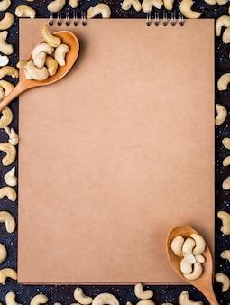 Bovenaanzicht van schetsboek en houten lepels met gezouten geroosterde pistachenoten op zwarte achtergrond