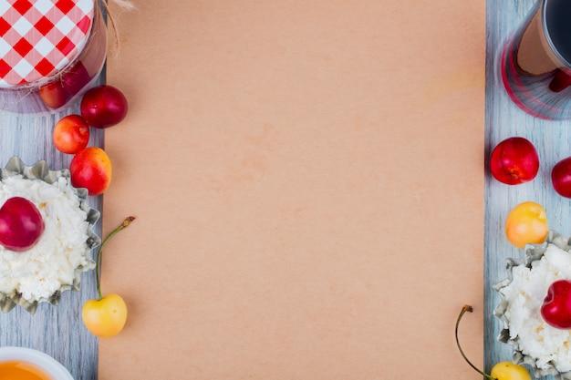 Bovenaanzicht van schetsboek en kwark met verse rijpe gele en rode kersen rond gerangschikt op grijs