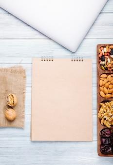 Bovenaanzicht van schetsboek en noten mix met walnoten amandel en zoete gedroogde dadels op houten tafel