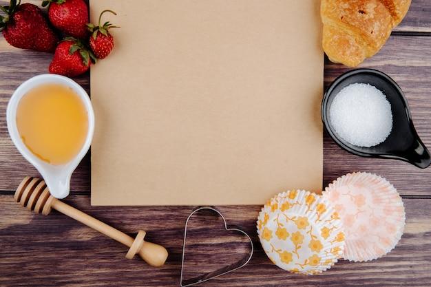 Bovenaanzicht van schetsboek en verse rijpe aardbeien met honing suiker croissant en cookie cutters op hout