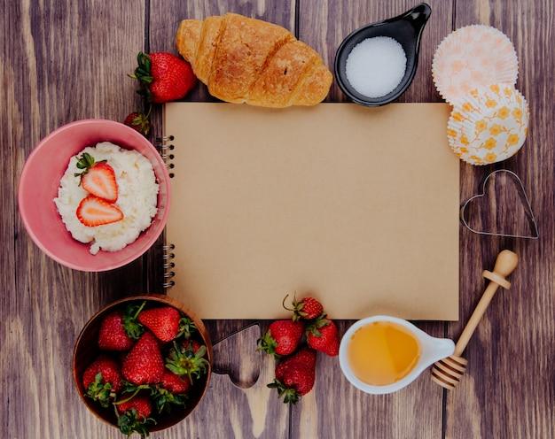 Bovenaanzicht van schetsboek en verse rijpe aardbeien met honing, suiker, croissant, kwark en koekjessnijders op hout