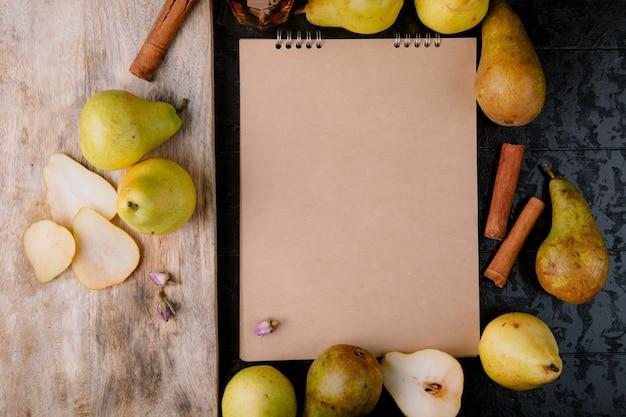 Bovenaanzicht van schetsboek gemaakt van ambachtelijk papier omlijst met verse rijpe peren en een houten snijplank met keukenmes en plakjes peren op zwarte achtergrond
