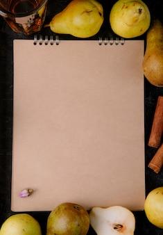 Bovenaanzicht van schetsboek gemaakt van kraftpapier omlijst met verse rijpe peren op zwarte achtergrond