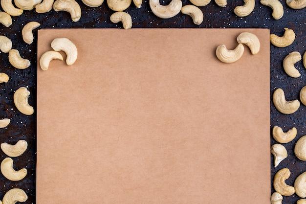 Bovenaanzicht van schetsboek met gezouten geroosterde pistachenoten verspreid op zwarte achtergrond