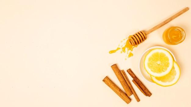 Bovenaanzicht van schijfje citroen; kaneel en honing over beige oppervlak