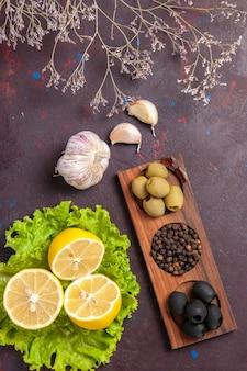 Bovenaanzicht van schijfjes citroen met olijven en groene salade op zwart