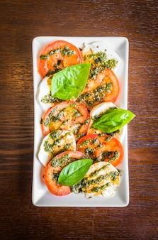 Bovenaanzicht van schijfjes tomaat met mozzarella