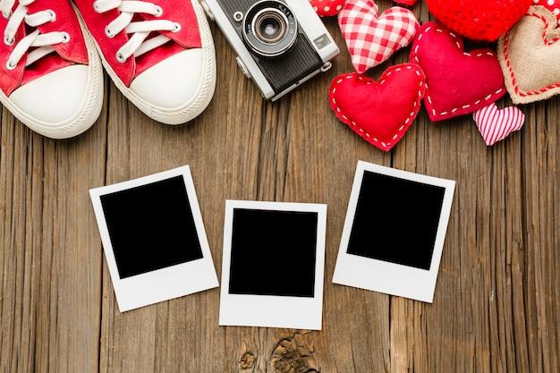 Bovenaanzicht van schoenen en polaroids met valentijnsdag ornamenten
