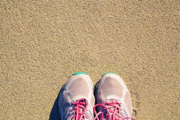 Bovenaanzicht van schoenen op de textuurachtergrond van het tropische zandstrand, kopieer de ruimte van het reisavontuurconcept.