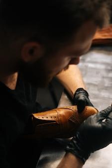 Bovenaanzicht van schoenmaker die zwarte latexhandschoenen draagt die oude lichtbruine leren schoenen met vod schoonmaakt