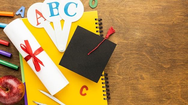 Bovenaanzicht van schoolbenodigdheden met academische pet en kopie ruimte