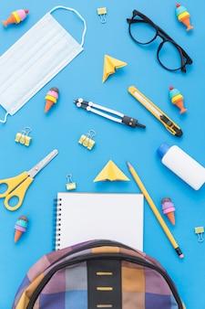 Bovenaanzicht van schoolbenodigdheden met boekentas en glazen