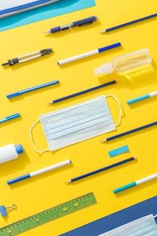 Bovenaanzicht van schoolbenodigdheden met potloden en gezichtsmasker