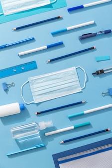 Bovenaanzicht van schoolbenodigdheden met veel potloden en gezichtsmasker