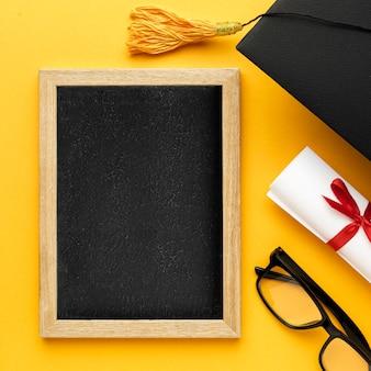 Bovenaanzicht van schoolbord met academische pet en glazen