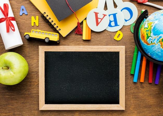 Bovenaanzicht van schoolbord met schoolbenodigdheden en appel