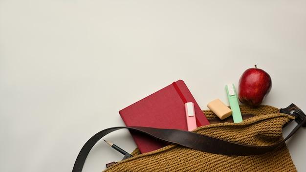 Bovenaanzicht van schooltas met boek