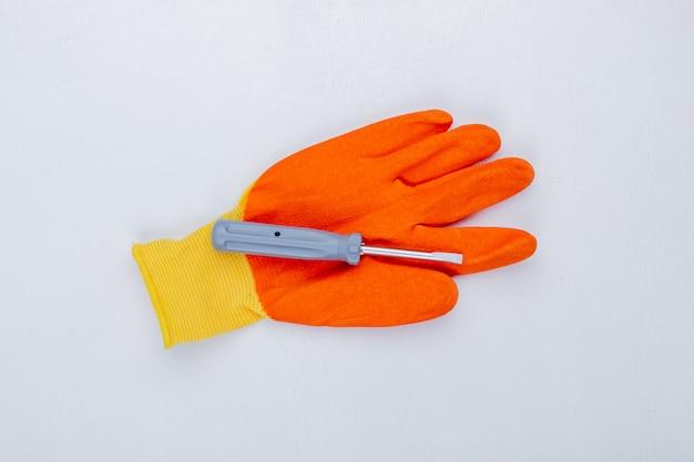 Bovenaanzicht van schroevendraaier op handschoen op witte achtergrond