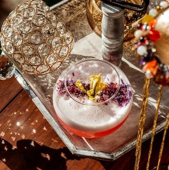 Bovenaanzicht van schuimend cocktailglas gegarneerd met gedroogde bloemblaadjes