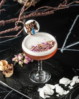 Bovenaanzicht van schuimende cocktail gegarneerd met rozenblaadjes stukken en eierschalen