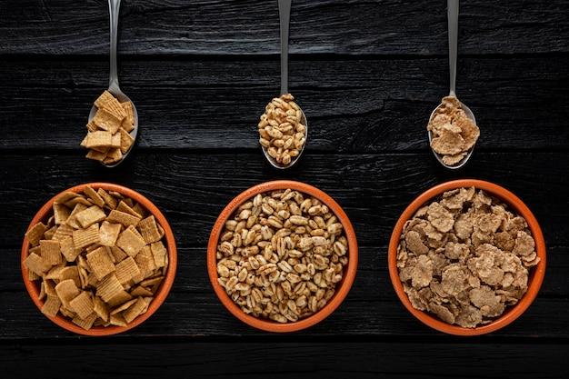 Bovenaanzicht van selectie van ontbijtgranen in kommen met lepels