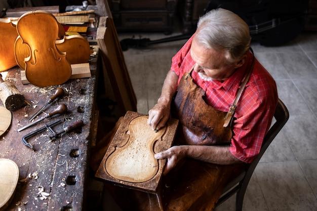 Bovenaanzicht van senior timmerman werkzaam in zijn ouderwetse werkplaats