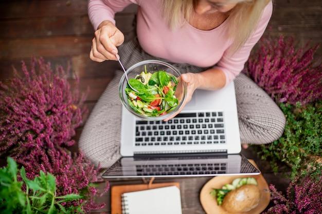 Bovenaanzicht van senior vrouw met laptop die buiten op het terras zit en een gezonde lunch eet.
