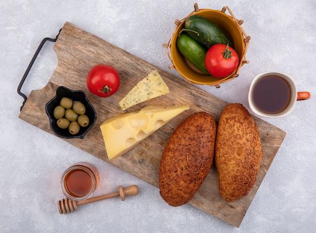 Bovenaanzicht van sesampasteitjes op een houten keukenbord met groene olijven op een zwarte kom met kaas en een kom met komkommers en tomaten op een witte achtergrond