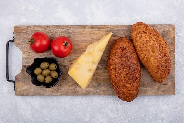Bovenaanzicht van sesampasteitjes op een houten keukenbord met groene olijven op een zwarte kom met tomaten en kaas op een witte achtergrond